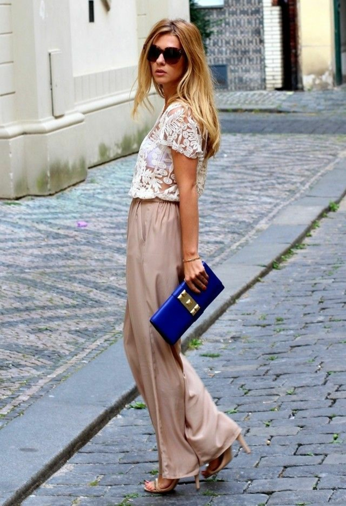 tenue invitée mariage, pantalon large en soie en couleur bronze, blouse en dentelle blanche aux manches courtes, pochette en bleu roi avec fermoir rectangulaire en couleur or