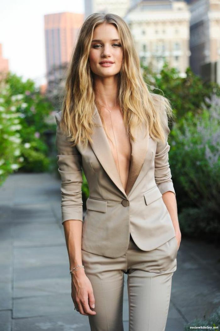 tenue ceremonie femme en tissu satiné kaki, veste courte avec la taille sublimée, pantalon moulant, manches veste retroussée, deux poches et un bouton pour la veste, grand décolleté ouvert en V, sans blouse en dessous