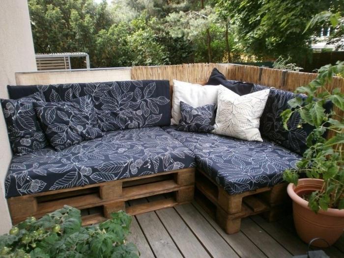 potager sur une terrasse en palette avec meuble d'angle couvert de coussins bleus aux motifs feuilles blancs
