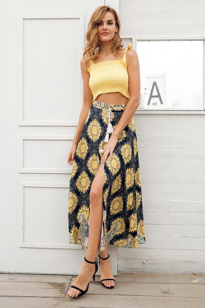 modèle de jupe mi-longue à taille haute de couleur noir et jaune, tenue de plage en jupe et top crop jaune avec bretelle