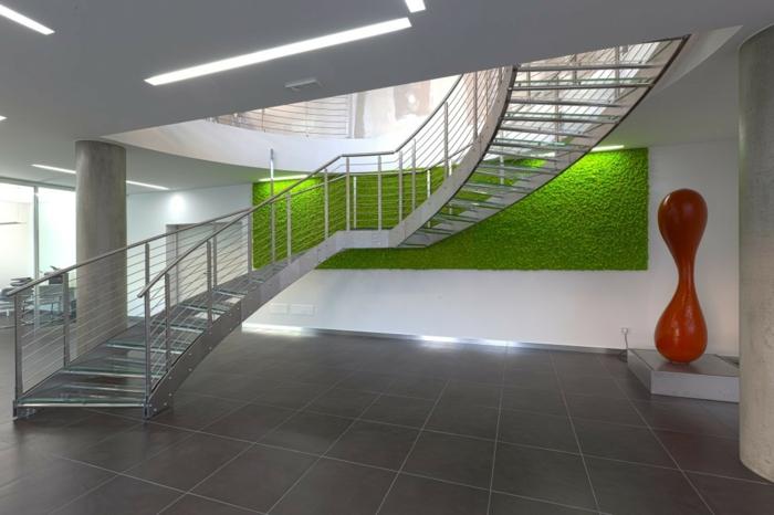 mur végétal intérieur, édifice public avec escaliers en demi-tournant en métal clair aluminium, sol recouvert de dalles de carrelage couleur taupe, oeuvre artistique abstraite, figure en rouge