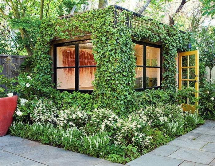 petit pavillon de jardin avec mur végétalisé, construction entièrement recouverte de plantes vertes, petite terrasse sur le toit, sol autour du pavillon recouvert d'herbe et de fleurs, sol de jardin autour du pavillon recouvert de dalles grises