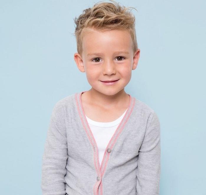 une coupe au dégradé sur les cheveux blond d un petit garçon, coupe enfant garcon moderne avec un dessus décoiffé