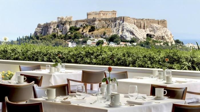 un mur végétalisé comme garde-corps dans un restaurant d'Athènes, chaises en marron clair, belle vue sur l'Acropole, ciel bleu sans nuages