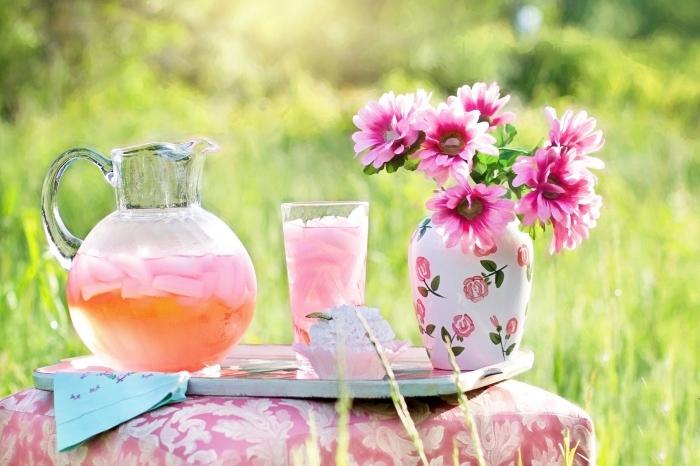 décoration de table pique-nique en plein air avec un ottoman rose et un plateau ancien, pichet citronnade rose et orange