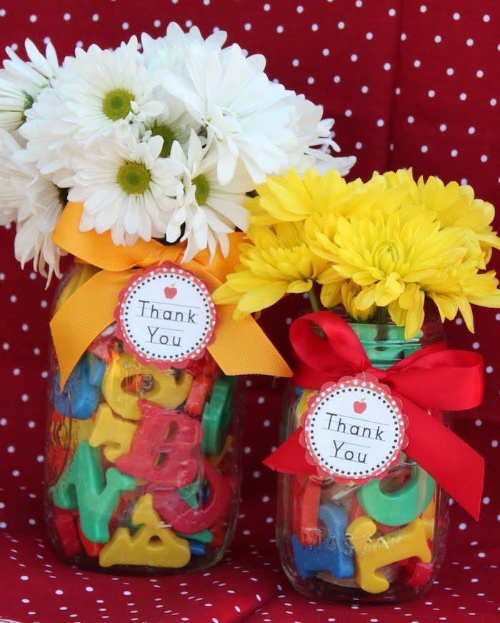 pot en verre rempli de lettres alphabet en plastique avec décoration de ruban et étiquette cadeau, bouquet de fleurs blanches et jaunes