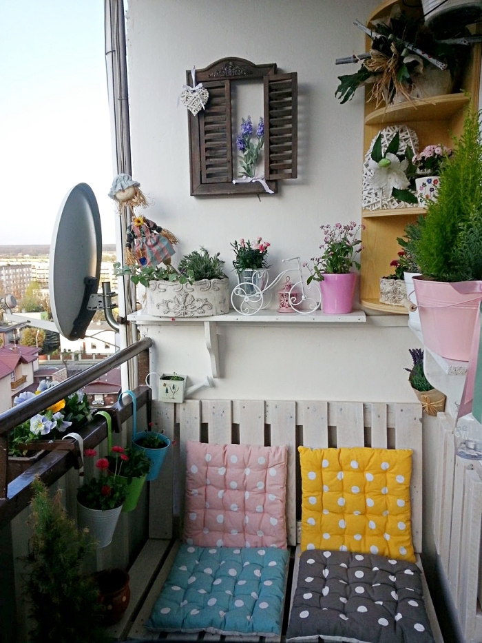 comment arranger une terrasse en palette avec meuble canapé couvert de coussins colorés et plusieurs objets décoratifs