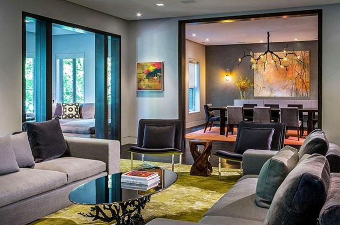 éléments de wengé couleur dans la déco, tapis vert, table basse ovale, sofas gris, murs bleus