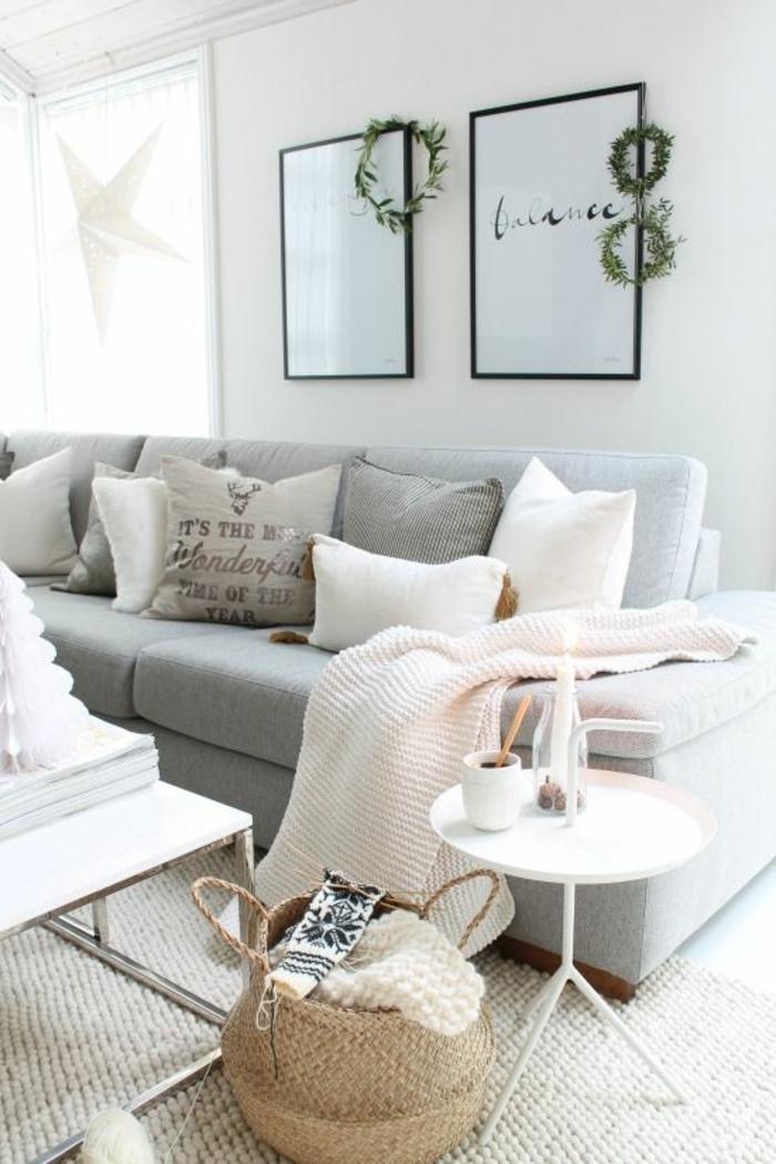 peinture rose poudré, deux tableaux avec des messages sympa aux cadres noirs, un canapé gris pastel, une moquette beige, une table ronde en métal, une corbeille de rangement en paille tressée