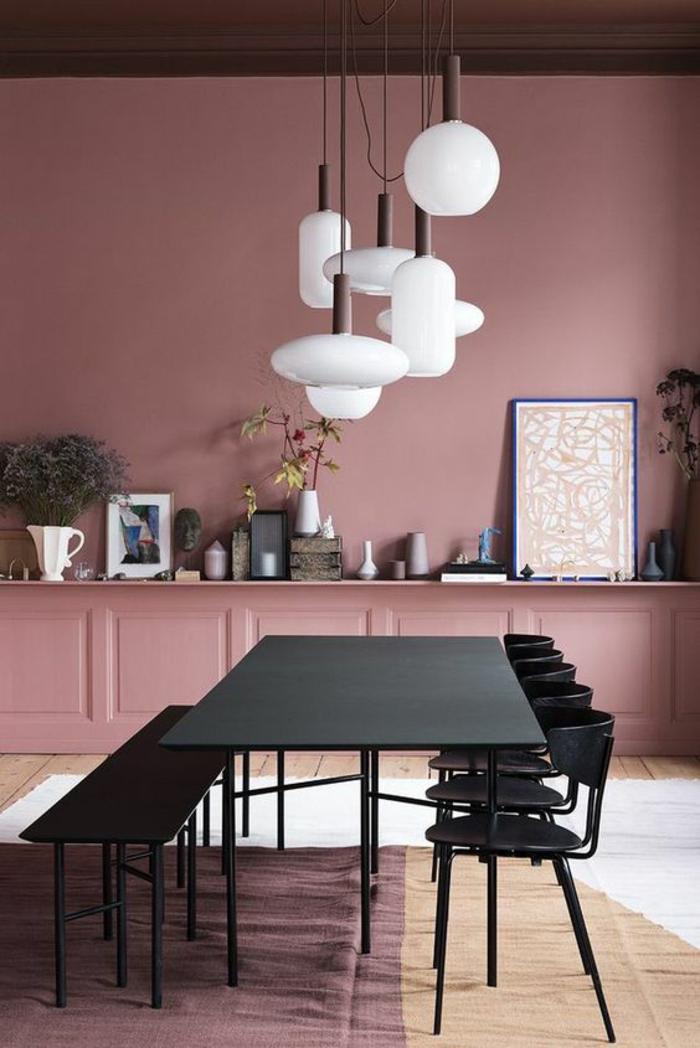 murs en vieux rose, rose noir et blanc, sept grands luminaires en verre blanc mat au-dessus d'une table rectangulaire noire, cinq chaises en métal et bois noir