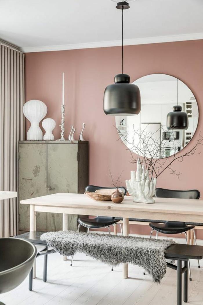 murs en couleur rose pale, luminaire en céramique noire suspendu sur un fil noir, grand miroir rond, table rectangulaire en bois clair