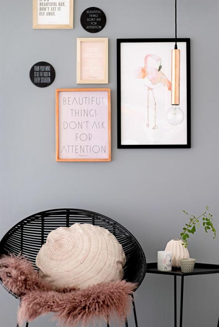 chambre rose poudré aux murs gris pastel, quatre tableaux de dimensions différentes, fauteuil au dossier rond en métal noir, couverture en nuance couleur poudre de roses, table ronde en métal noir