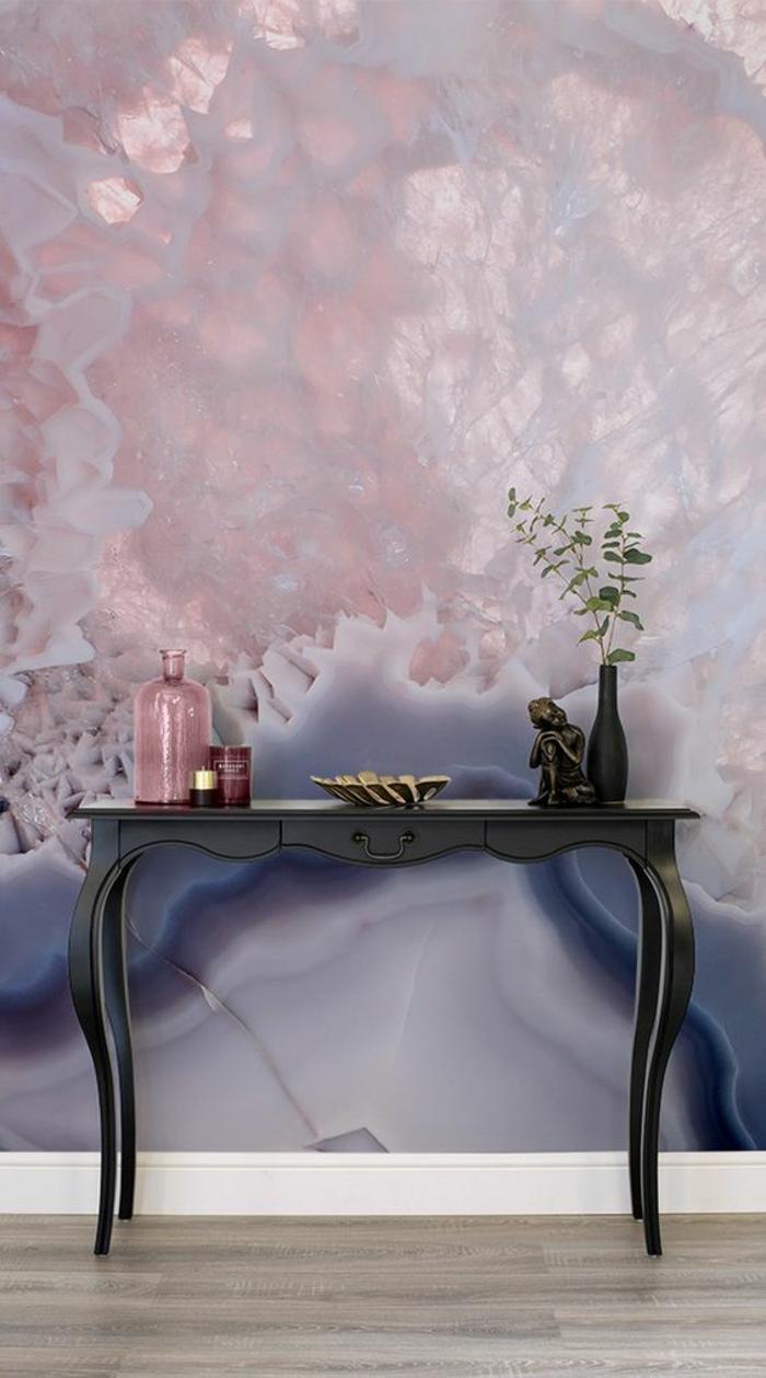 murs au papier peint aux effets 3D, nuances nacrées en couleur rose pale et bleu saphir, meuble d'entrée en bois peint en noir, avec petit vase noir et bocal en couleur rose poudré