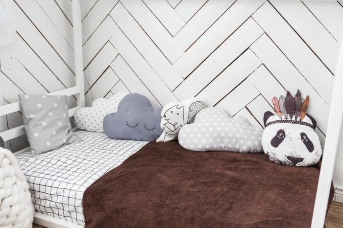 lit cabane montessori dans un angle de la chambre montessori, cabane lit en bois blanc, coussins en formes diverses, murs revêtus en bois blanc encastré comme un parquet