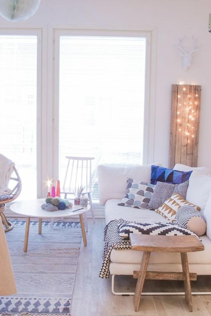 guirlande lumineuse led dans un angle, installée sur un panneau en bois brut, décoration scandinave, petite table basse ronde au centre de la pièce