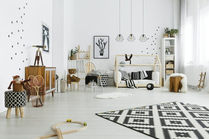 lit cabane montessori, cabane enfant lit en bois clair, petite taille, tapis aux losanges noirs et blancs, murs blancs aux pois noirs, étagère colonne blanche avec des paniers de rangement