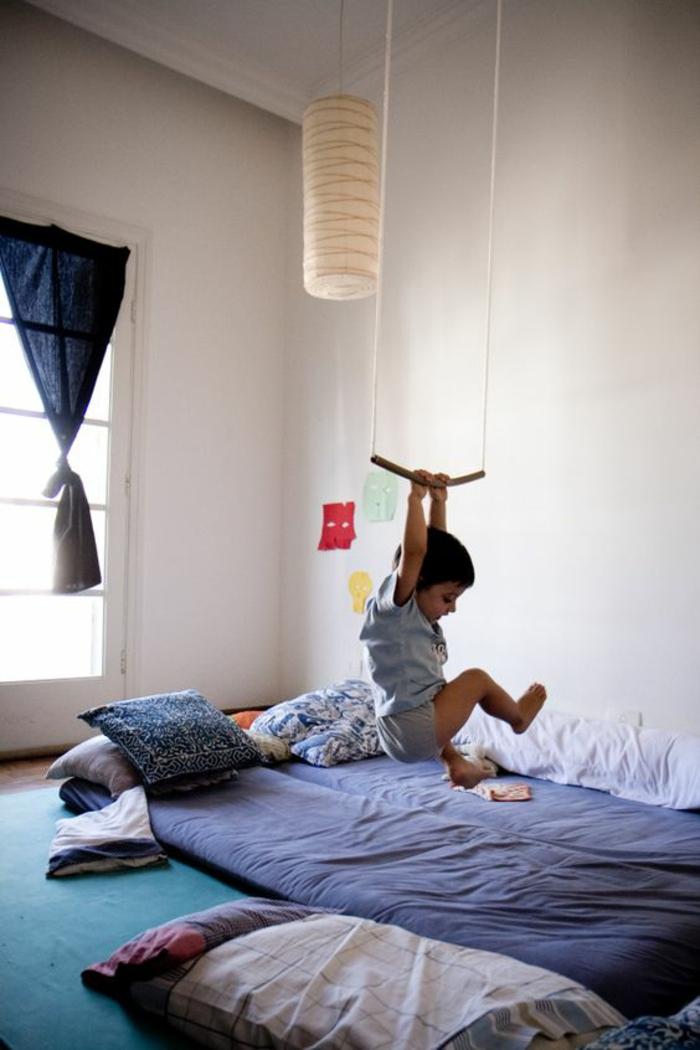 lit bébé sans barreau, matelas bleu marin, balançoire suspendue au plafond, enfant qui se balance, luminaire style chinois forme cylindrique en couleur blanc crème, chambre montessori