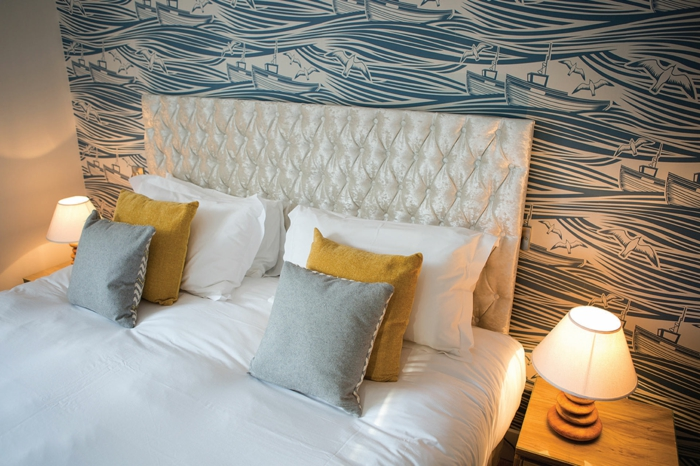 un meuble en bois, tete de lit originale, revêtue en tissu satiné en nuances irisées avec des effets matelassés, mur couvert de papier peint en couleurs bleue et blanche, motifs mer aux grosses ondes et des petits bateaux qui se démènent