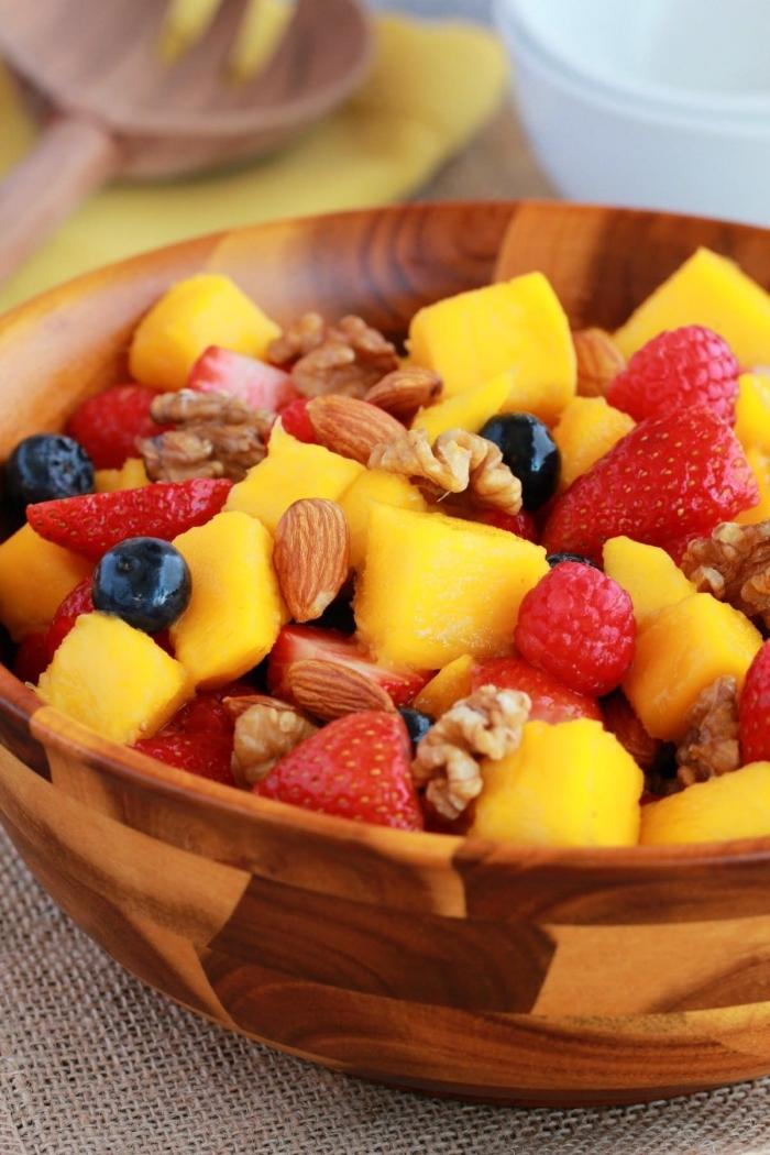 recette salade de fruits frais et nourrissante, à la mangue et aux fruits rouges, avec amandes et noix