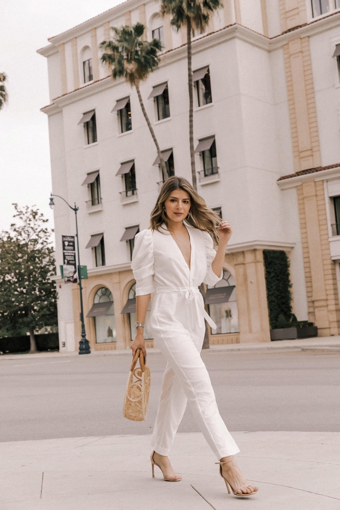 jolie combinaison blanche élégante aux manches courtes et décolleté en V combinée avec sac à main et sandales beige