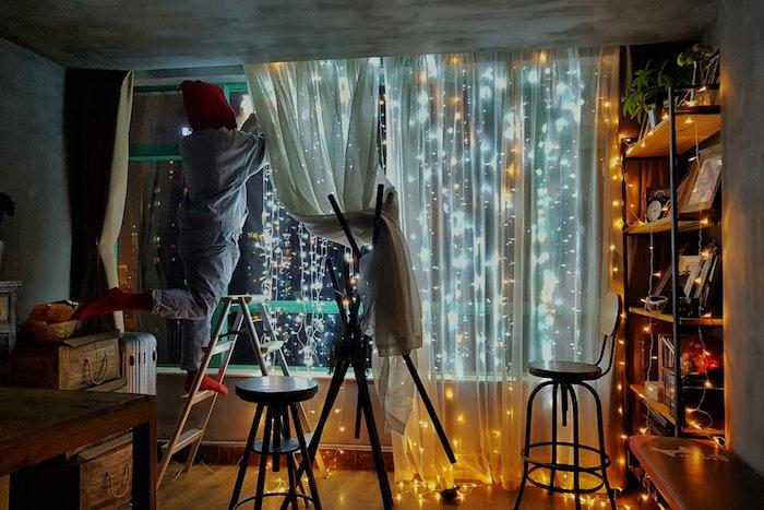 Idée d'aménager une petite chambre, idees pour la deco petite chambre adulte cocooning, guirlandes lumineuses, femme sur échelle qui créée de la décoration festive