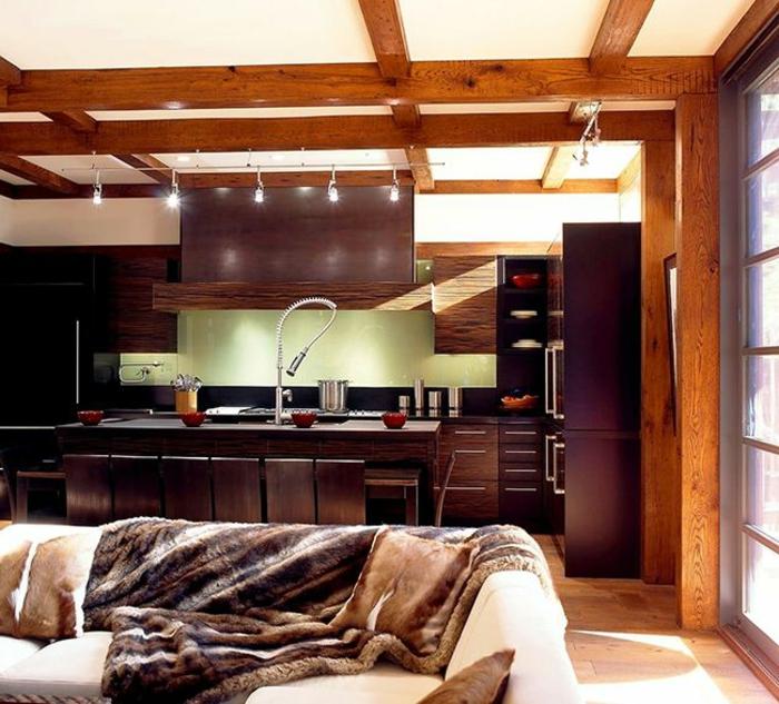 équipement moderne salon, poutres apparentes, canapé et couvre-lits fourrure, cuisine avec ilot