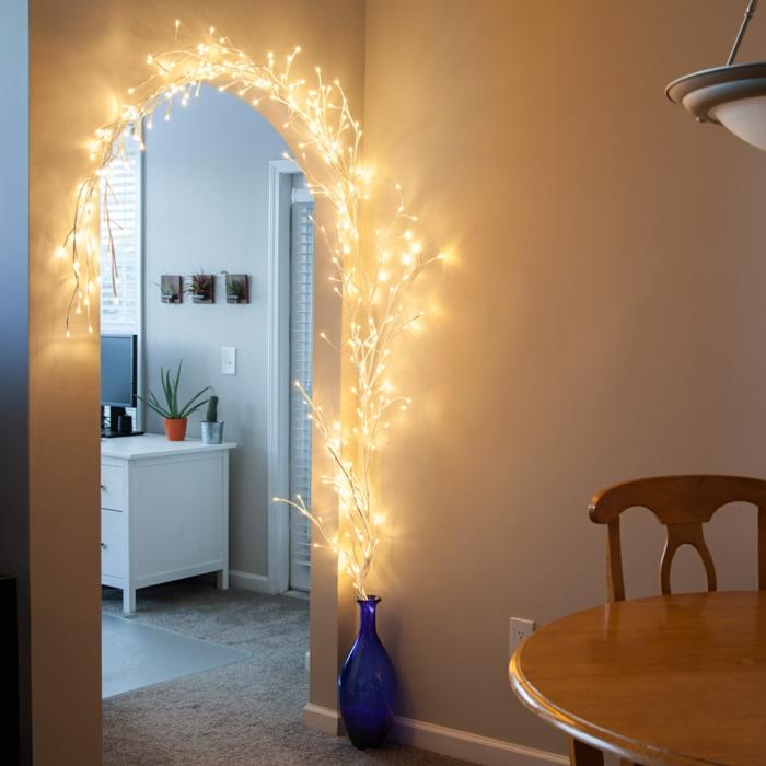 idée déco chambre cocooning, guirlande lumineuse chambre en forme de branches fines d'arbre qui entourent le cadre ovale d'un arc d'entrée