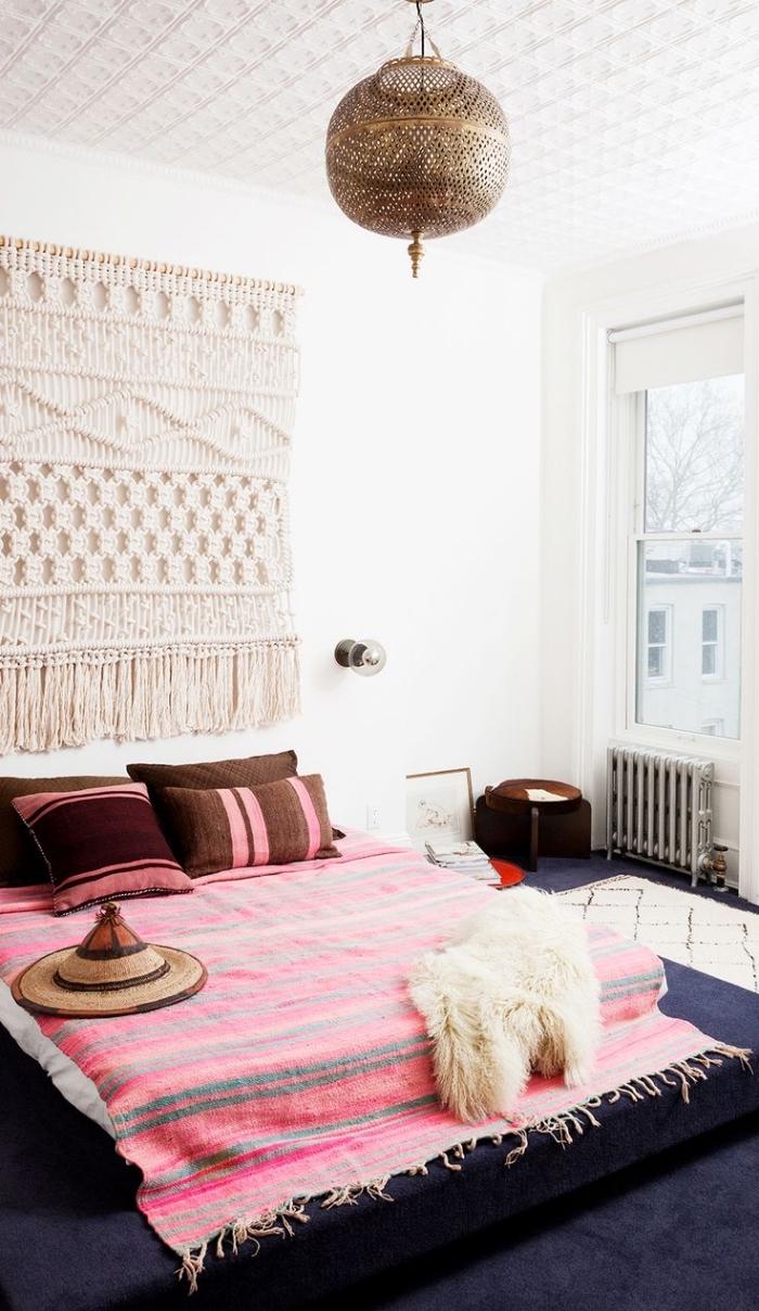 déco boheme chic avec suspension murale macramé et plaid rayé en gris clair et rose avec franges, modèle de lit au sol couvert de plaid et coussins décoratifs