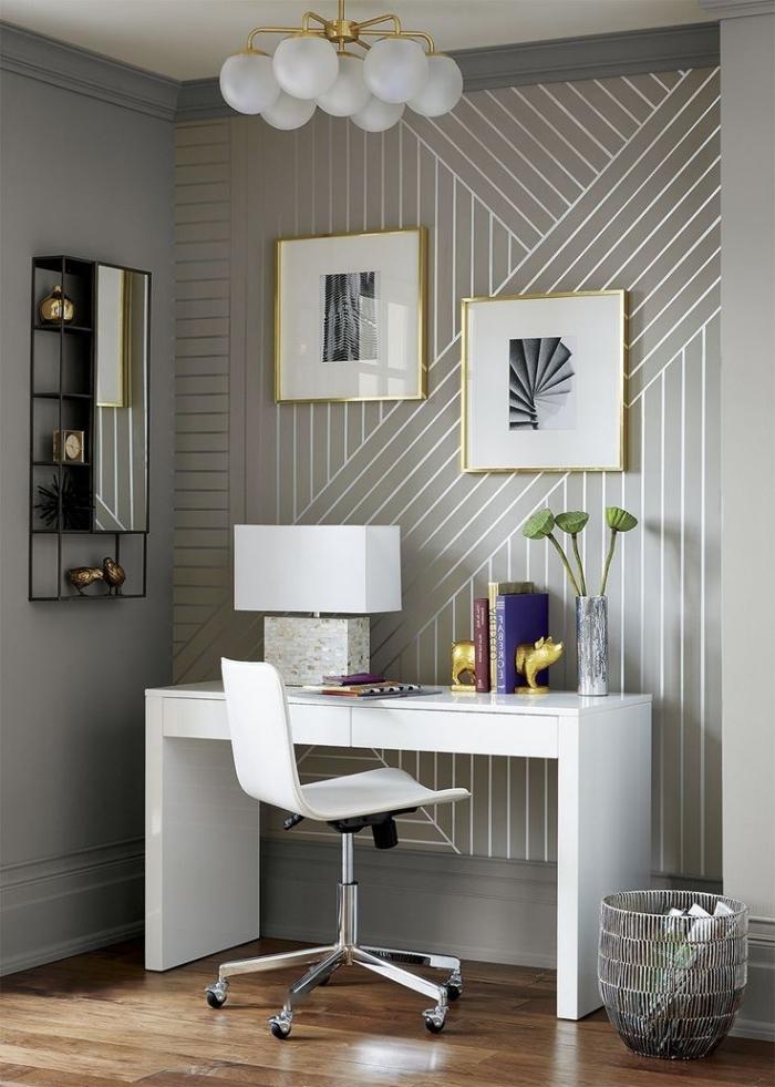 lé de papier peint à motifs graphiques métallisés derrière le bureau pour délimiter l'espace bureau