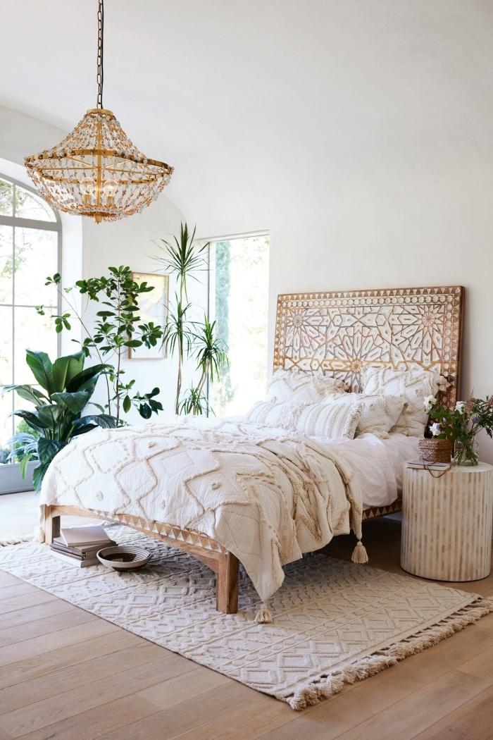design chambre à coucher de style bohème aux murs blancs avec plancher de bois clair et tête de lit de bois à design mandala