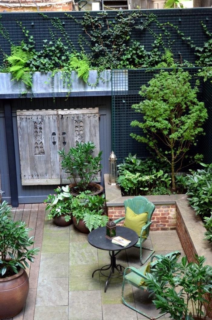 ambiance apaisante et rassérénante dans une cour intérieur dont les murs sont couverts de grillage pour plantes grimpantes