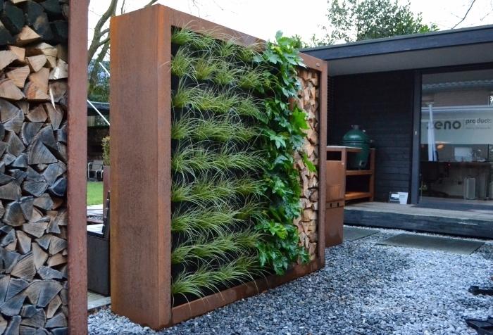 idée originale pour l'aménagement d'un petit jardin, une construction en bois abritant un mur végétal et des bûches