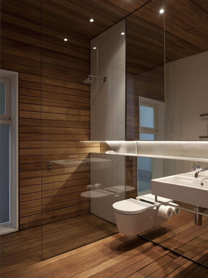 idée agencement petite salle de bain à revêtement imitation bois avec large miroir à rangement et cuvette wc suspendue