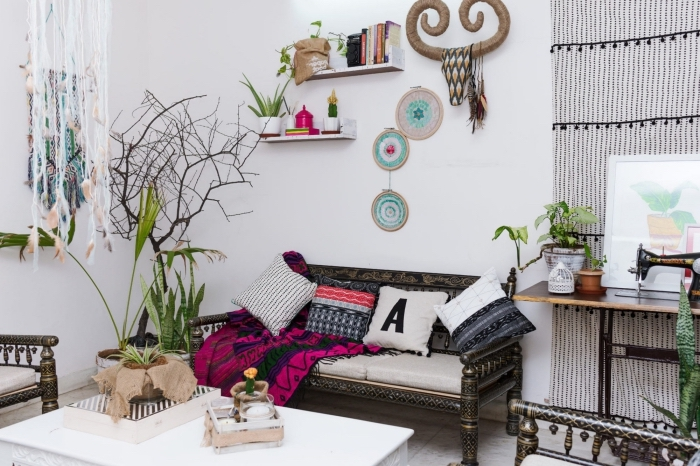 modèle de design intérieur de style boho chic dans un studio aux murs blancs, accessoires boho chic multicolore aux motifs ethniques