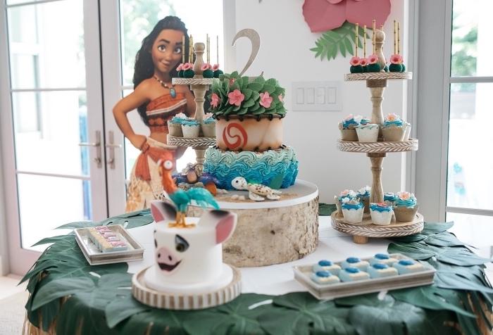 decoration gateau vaiana sur trois étages avec crème au beurre de couleurs bleus, modèle de fleurs roses avec feuilles vertes en pâte à sucre