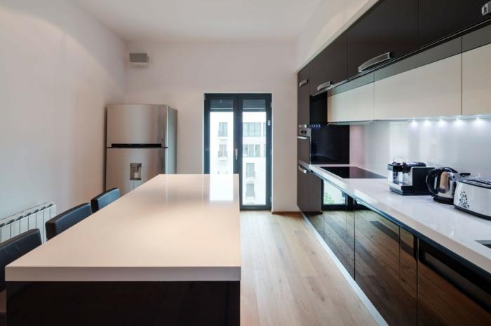 cuisine en couleurs contrastes, grand îlot central avec comptoir blanc, équipement minimaliste-bois-wengé