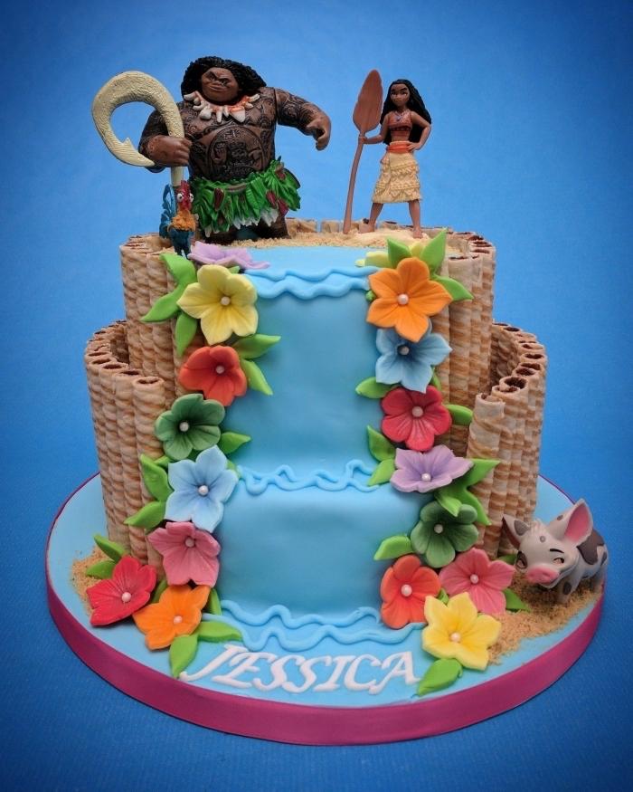 gateau vaiana à deux étages à design cascade d'eau décorée de fleurs en pâte à sucre colorées avec figurines Maui et Vaiana