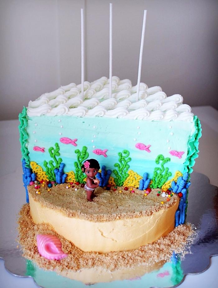 superbe déco de gâteau DIY d'inspiration bébé Vaiana avec deux étages à design sable en biscuits et océan à figurines poissons en pâte sucre