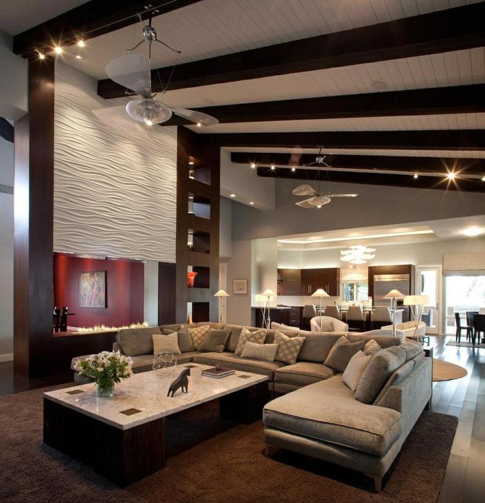 grande table plateau marbré, poutres en couleur wengé, cheminée murale ouverte, sofa en U couleur taupe