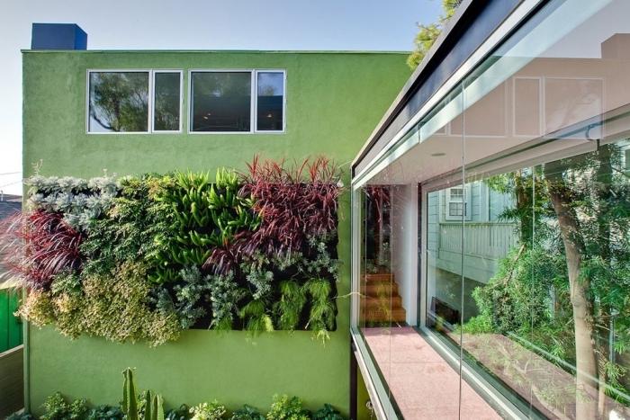 maison d'architecture moderne avec façade végétalisée avec des plantes variées de taille et de couleur différente en parfait accord avec le passage en verre