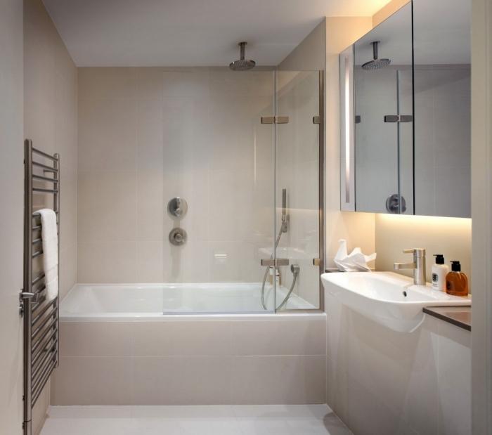 éclairage doux pour aménagement petite salle de bain avec baignoire et douche, modèle de carrelage couleur neutre