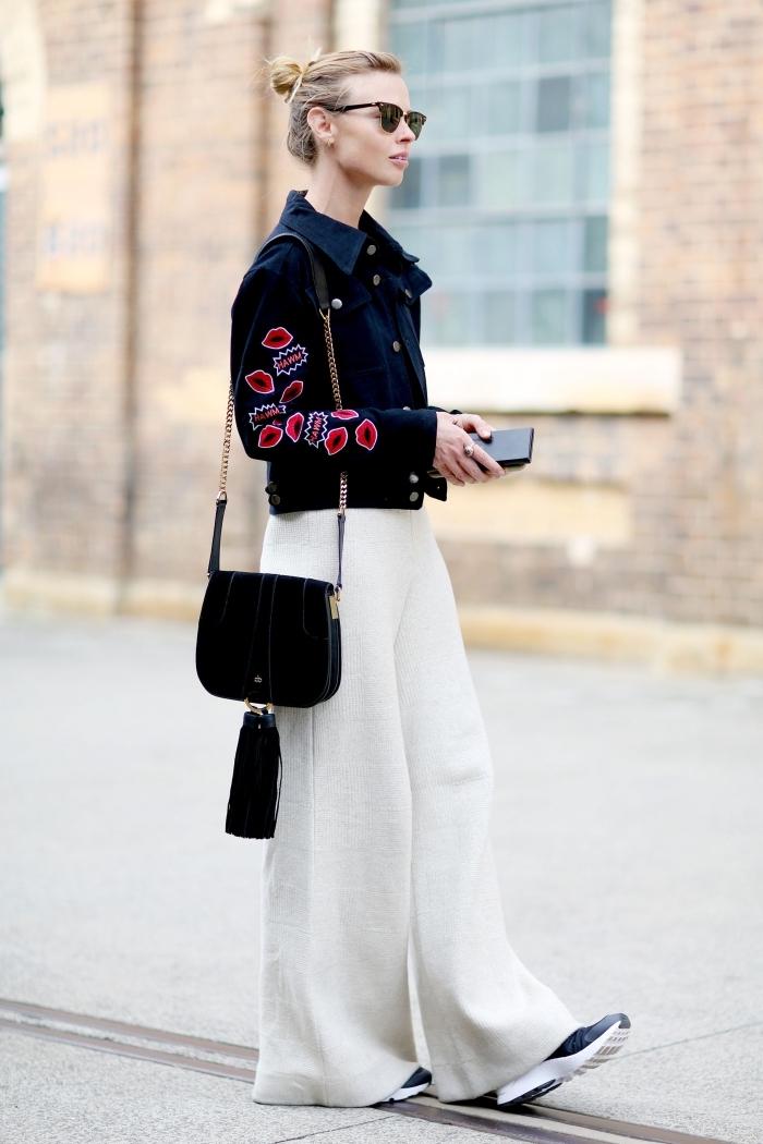 modèle de veste noir à décoration rouge assorti avec pantalon blanc design fluide, accessoires noires sac à main et lunettes de soleil