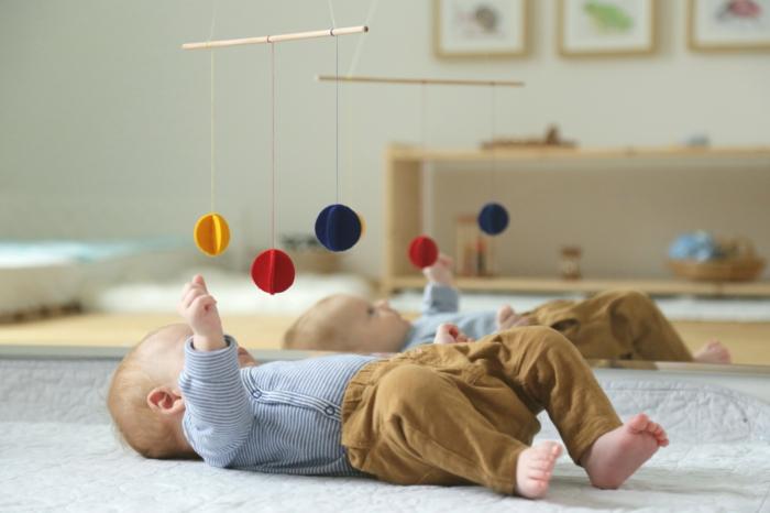 lit montessori, chambre montessori, lit cabane montessori, miroir montessori, meuble mobile avec des boules multicolores pour éveiller les sens