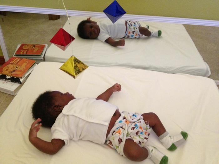 miroir et bébé qui se regarde en face, lit bébé sans barreau, miroir montessori, pyramide jaune brillante, jeux mobiles en formes géométriques, ronds, losanges et triangles, livres d'enfant,