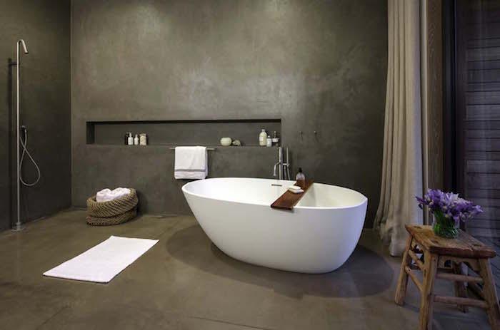 salle de bain tout en béton ciré sur sol et murs gris anthracitre avec baignoire ilot et douche italienne déco design