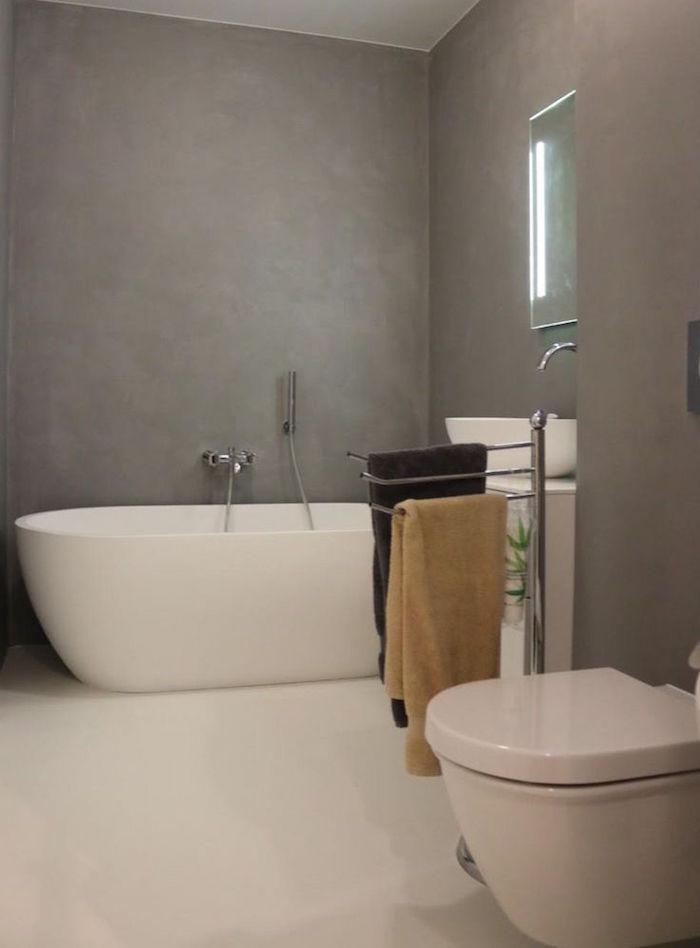 sdb rénovée style moderne avec mur en gris béton ciré sol carrelage blanc et baignoire ilot ovale