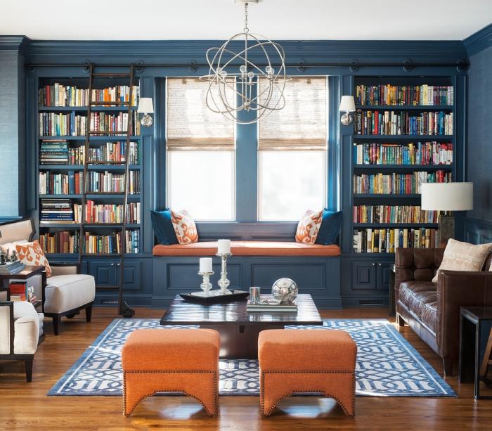 salon d'esprit british avec un mur bibliothèque peint en couleur bleu marine dont la luminosité est mise en avant pars les tons neutre et les touches d'orange