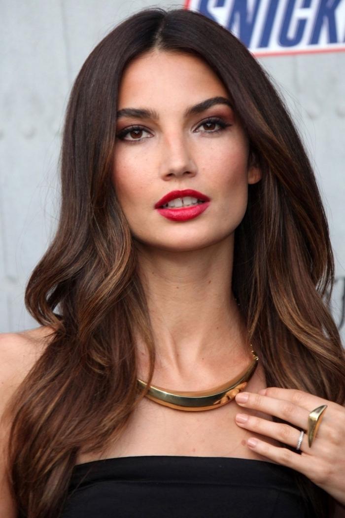 collier et bague à design massif et or, modèle de robe bustier avec bretelles de couleur noire, balayage sur cheveux chatain