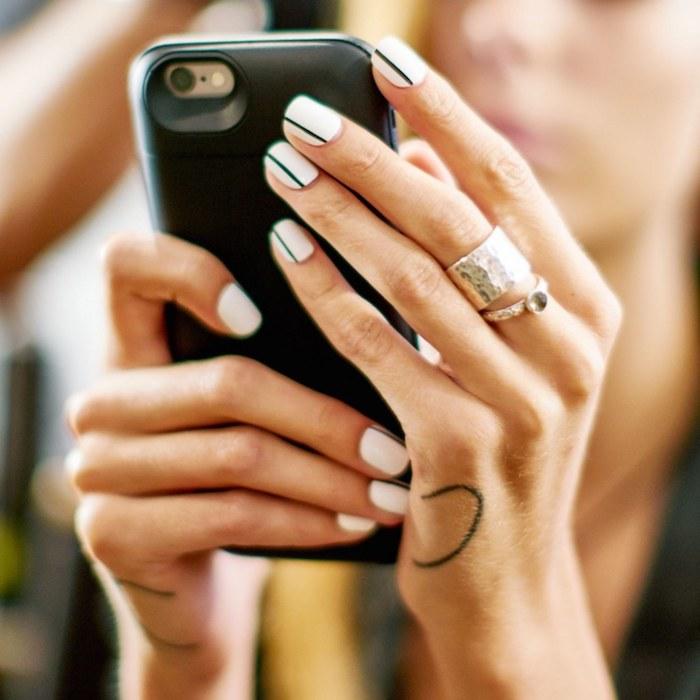 Motif ongle en gel géométrique, ligne noire sur base blanche, deco ongle gel, iphone dans les mains, femme tatouée, idée déco ongle originale
