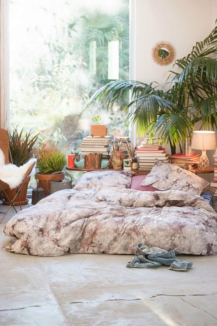 ambiance exotique dans une chambre boheme aux murs blancs aménagée avec lit au sol et meuble de bois pour rangement livres